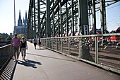 padlocks on fence of footpath of Hohenzollern railway bridge, Cologne, Germany. Young couples seal their their love with engraved padlocks and throw the key into the flowing river Rhine below, a tradition brought there from the Ponte Milvio bridge at Rome