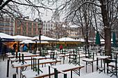 Snow-covered beer tables, Viktualienmarkt, Munich, Bavaria, Germany