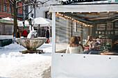 Restaurant and fountain of Karl Valentin at Viktualienmarkt in winter, Munich, Bavaria, Germany