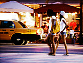 Two young women walking down the street at night in front of restaurants, Miami, Florida, USA