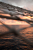 Sunset view through bowsprit net of sailing cruiseship Star Flyer (Star Clippers Cruises), Pacific Ocean, near Costa Rica, Central America, America