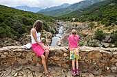 Mother and daughter sitting on old genovese stone bridge over Fango river, Fango Valley, Corsica, France, Europe