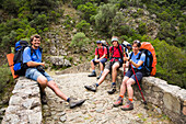 hikers on the old genovese stone bridge over the River Porto near the village of Ota, Spelunca Gorges, Corsica, France, Europe, not free for advertising