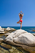 Woman exercising yoga on a rock, Palombaggia, Corsica, France
