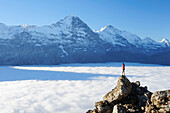 Woman standing on rock and looking towards Eiger and Jungfrau above sea of fog, Bussalp, Grindelwald, UNESCO World Heritage Site Swiss Alps Jungfrau - Aletsch, Bernese Oberland, Bern, Switzerland, Europe