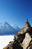 Woman sitting on rock and looking towards Eiger and Jungfrau above sea of fog, Bussalp, Grindelwald, UNESCO World Heritage Site Swiss Alps Jungfrau - Aletsch, Bernese Oberland, Bern, Switzerland, Europe