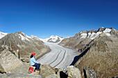 Woman looking towards glacier Grosser Aletschgletscher with Jungfrau, Moench, Eiger and Wannenhorn, Eggishorn, UNESCO World Heritage Site Swiss Alps Jungfrau - Aletsch, Bernese Alps, Valais, Switzerland, Europe