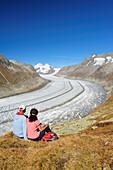 Couple looking towards glacier Grosser Aletschgletscher with Moench and Eiger, Grosser Aletschgletscher, UNESCO World Heritage Site Swiss Alps Jungfrau - Aletsch, Bernese Alps, Valais, Switzerland, Europe