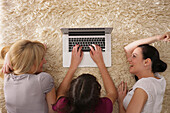 Three young women using a laptop while lying on a carpet, Munich, Bavaria, Germany