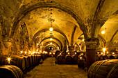 Candlelit barrels inside wine cellar of Eberbach abbey, a medieval monastery at Eltville am Rhein, Rheingau, Hesse, Germany, Europe