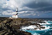 Cap de Favaritx Lighthouse FAVARITX MENORCA Black and white striped lighthouse building on rocky headland