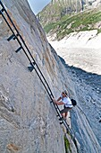 Elijah Weber climbs a steel ladder via ferrata on the Mer de Glace Glacier near Montenvers high above the city of Chamonix France