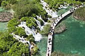 The Plitvice Lakes in the National Park Plitvicka Jezera in Croatia Visitors on the plank paths of the national Park The Plitvice Lakes are a string of lakes connected by waterfalls They are in a valley, which becomes a canyon in the lower parts of the