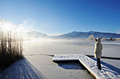 Woman standing on snow covered landing stage and looking towards lake Eichsee with sheet of ice, Herzogstand and Heimgarten in background, lake Eichsee, Bavarian foothills, Upper Bavaria, Bavaria, Germany, Europe