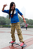 Chinese girl riding a special skateboard, leisure time, public square in front of the Walmart Shopping centre, Shapingba District, Chongqing, People's Republic of China