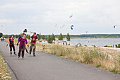 In-line skaters, kite surfers at Cospuden Lake in background, Leipzig, Saxony, Germany