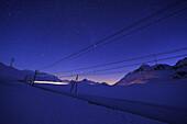 Train of Rhaetien railway as light beam driving by night through winter landscape to Berninapass, UNESCO World Heritage Site Rhaetien Railway, Raetien Railway, Albula-Bernina-line, Bernina range, Upper Engadin, Engadin, Grisons, Switzerland, Europe