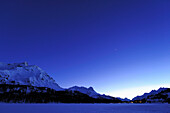 Night sky above snow-covered lake Silser See, with view to Malojapass, lake Silser See, Bernina range, Upper Engadin, Engadin, Grisons, Switzerland, Europe