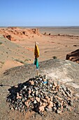Ritual place obo overlooking erosion formations at Bayanzag flaming cliffs, Gobi desert, Mongolia