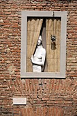 Artwork of a naked woman at window in the Bruco district Siena historic center, Siena, Italy
