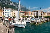 The holiday resort town of Gargnano on Lake Garda, Lombardy, Italy Sail boat leaving the harbour Lago di Garda