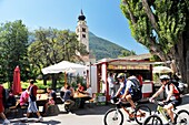 Cyclists outside the Mediaeval walled town of Glurns in the Val Venosta, Italian Alps Café and church of San Pancrazio
