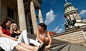 Women relaxing on the steps of the Konzerthaus Berlin, Gendarmenmarkt, Mitte, Berlin, Germany