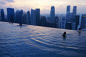 People swimming and admiring the view of the Central Business District from the Sands SkyPark Infinity Pool, Marina Bay Sands Hotel, Singapore, Asia