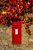 Red post box in wall, Thwaite, Yorkshire, UK - England