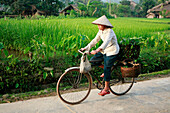 Woman cycling through village of Me, Ha Giang - near, Vietnam
