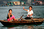 Local children in rowing boat, Ha Long Bay, Vietnam