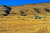 Land Rover on arid grassland road, Namibia