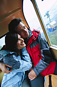 Mid adult couple looking out of a cabin of an overhead cable car, Upper Bavaria, Germany