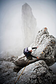 Female mountaineer at Kopftoerlgrat, Kapuzenturm in background, Ellmauer Halt, Kaiser Mountain Range, Tyrol, Austria