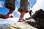 Two barefoot women on summit of mount Grosslitzner, Silvretta mountain range, Vorarlberg, Austria