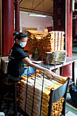 Young woman working in a Chinese Temple, Kuala Lumpur, Malaysia, Asia
