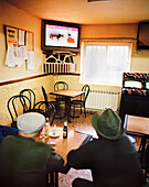 Two old men watching tv in one of the two bars in San Martin del Pimpollar, Sierra de Gredos, Castile and Leon, Spain