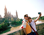 Couple taking photographs of themselves on Puente de Piedra, Saragossa, Aragon, Spain