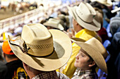 Young boy looking at man, Spectators at the rodeo, middle west, Rodeo, Minot, North Dakota, United States of America, USA