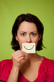 Mid audlt woman holding smiling postit note