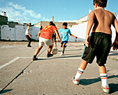 Kids playing football between ragged houses, harbour of Ponta Delgada, southern coast of Sao Miguel island, Azores, Portugal