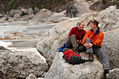 Couple having a rest on rocks at Little Oberon Bay, Wilsons Promontory National Park, Victoria, Australia
