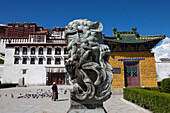Lion statue in front of the Potala Palace, residence and government seat of the Dalai Lamas in Lhasa, Tibet Autonomous Region, People's Republic of China