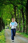 Woman jogging through an alley, Upper Bavaria, Bavaria, Germany