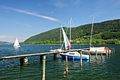 Wooden landing stage with sailing boats leading into lake Ossiacher See, Bodensdorf, lake Ossiacher See, Carinthia, Austria, Europe