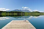 Sneakers standing on wooden landing stage in lake Turnersee, Karawanken range in background, lake Turnersee, Carinthia, Austria, Europe