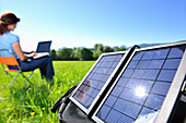 Woman sitting on a meadow while using a laptop, solar panel in foreground, Bavaria, Germany