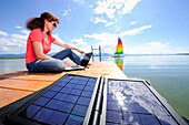 Woman using a laptop on a jetty at lake Chiemsee, solar panels in foreground, Chiemgau, Upper Bavaria, Bavaria, Germany