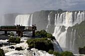 tourists on platform looking down over iguazu falls on the brazilian side iguacu national park, parana, brazil, south america