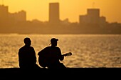 Local musician playing blues music at Goree island during sunset. Background, capital city Dakar. Senegal, West Africa